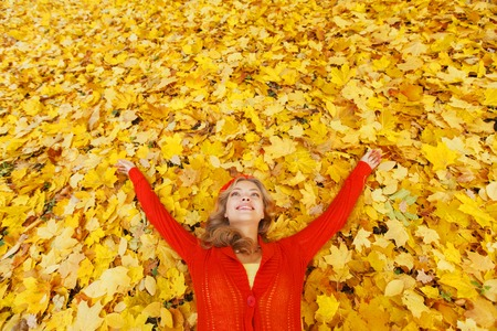 Happy young beautiful woman laying on dry autumn leaves photo