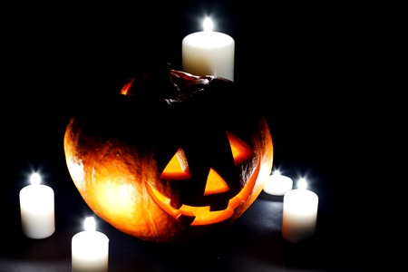 Halloween pumpkin surrounded with candles isolated on black background photo