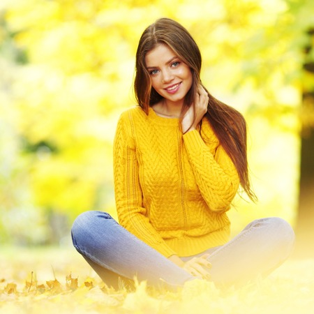 Portrait of a gorgeous brunette woman sitting in the autumn park photo