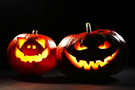 Two glowing Halloween pumpkins isolated on black background photo
