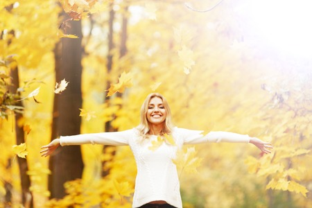 Happy woman posing in autumn park on yellow trees background photo