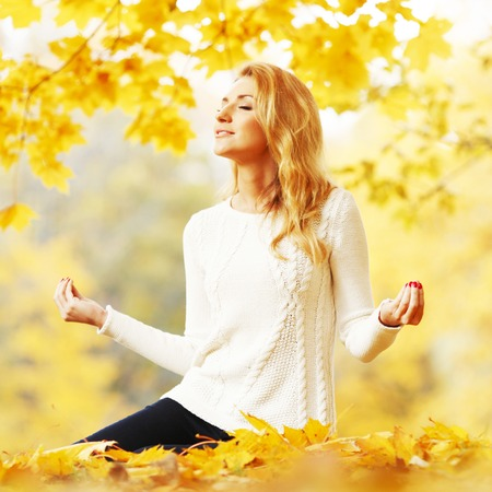 Beautiful young woman sitting in autumn park in lotus yoga position photo
