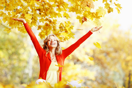 Happy woman in autumn park drop up leaves photo