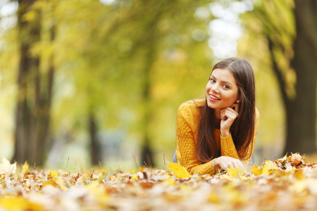 Girl laying on leafs in the autumn park photo