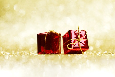 Small decorative red presents on golden glitter background photo
