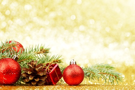 Christmas card with fir tree branch and decoration on golden glitter background Фото со стока