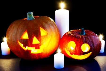 Halloween pumpkins and candles isolated on black background photo