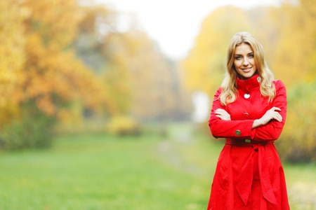 Young woman in red coat walking in autumn park photo