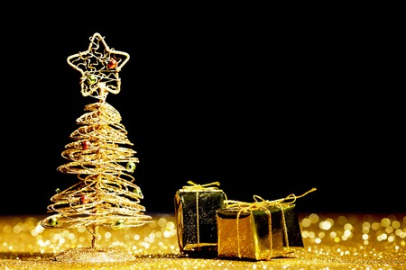Toy golden decorative Christmas tree on glitter background photo