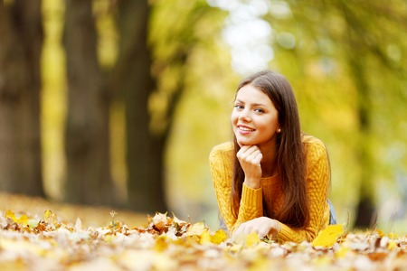 Young cute woman laying on dry leaves in autumn park photo