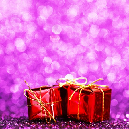 Decorated red holiday gifts on glitter background photo