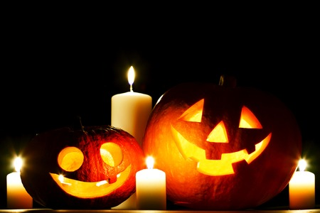 Funny Halloween pumpkin and burning candles on black background photo