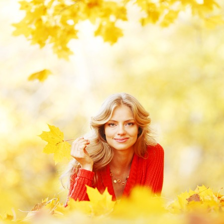 Beautiful young woman laying on yellow leaves in autumn park photo