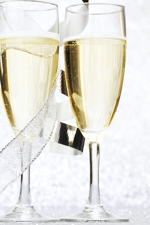 Two glasses of champagne with bow on silver background photo