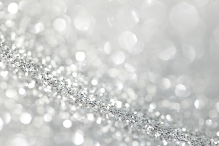 silver backgrounds: Silver festive glitter background with defocused lights Stock Photo