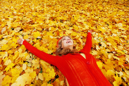 Happy young woman laying on autumn leaves in park photo
