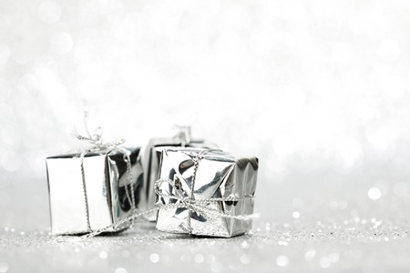 Decorative silver boxes with holiday gifts on shiny glitter background photo