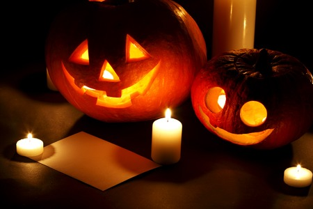 Halloween pumpkins with candles and post card isolated on black background photo