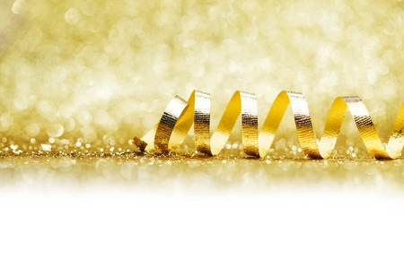 glitter background: Golden curly ribbon decoration on glitter background close-up