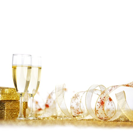 Glasses of champagne and presents on golden glitter background photo
