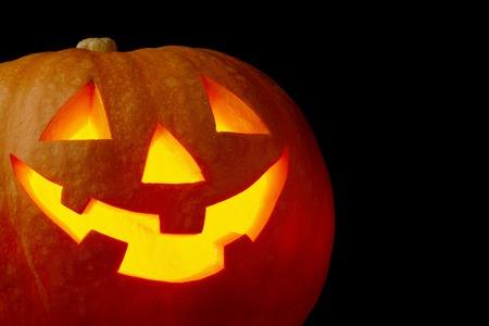 scary face: Illuminated cute glowing halloween pumpkin on black background Stock Photo