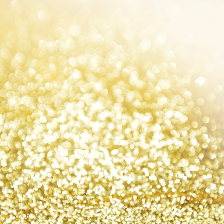 Golden festive glitter background with defocused lights photo