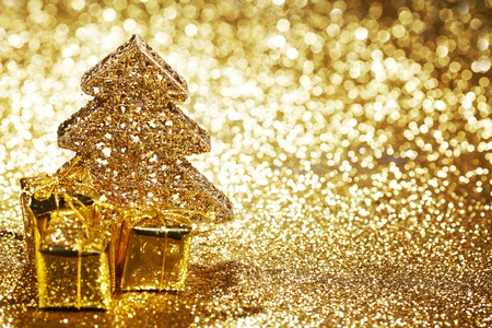 Beautiful golden decorative christmas tree and gifts on golden glitter background photo