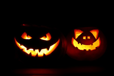 Two carved Halloween pumpkins jack-o-lantern on dark background photo