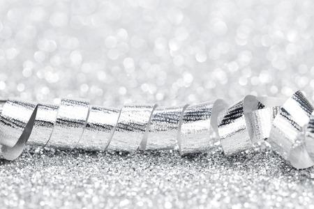 Shiny silver gift ribbon on bokeh background close-up photo