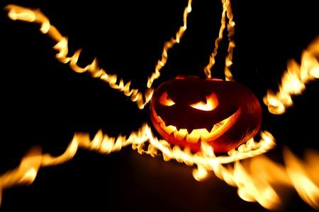 Burning halloween pumpkin on black background photo