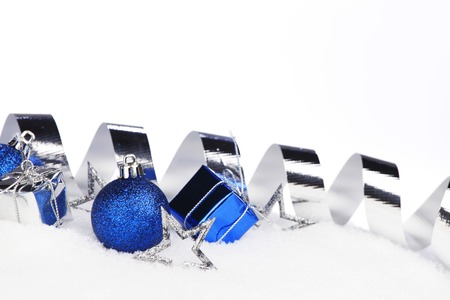 Silver and blue Christmas decorations on snow close-up photo