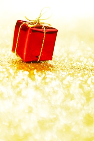 Decorative red box with holiday gift on shiny glitter background photo