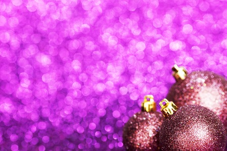 Beautiful purple christmas balls on abstract glitter background close-up photo