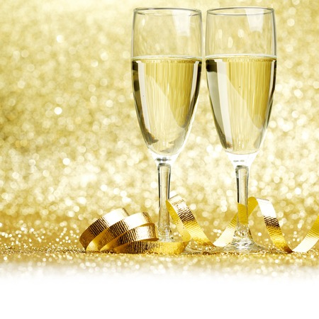 Glasses of champagne and curly decorative ribbon on golden glitters photo