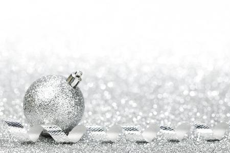 Christmas decorative ball on light silver bokeh background photo