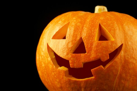Funny Halloween pumpkin isolated on black background photo