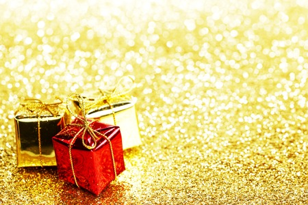 Decorative red and gold boxes with holiday gifts on shiny glitter background photo