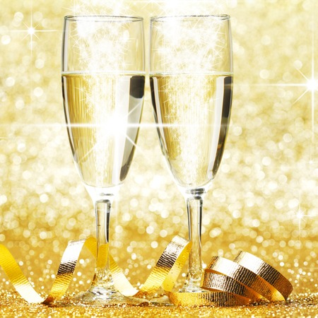 Glasses of champagne and ribbon on golden glitters photo