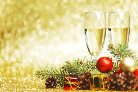 Champagne, fir tree, christmas decor and gifts on golden background photo
