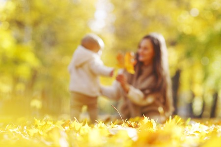 Beautiful young mother and her daughter in autumn park photo