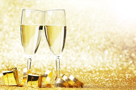 Champagne in glasses and gift boxes on golden background photo