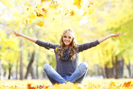 Portrait of beautiful young woman sitting outdoors in autumn park photo