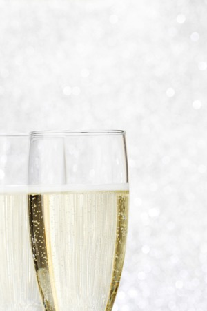 Two champagne glasses on silver bokeh background photo