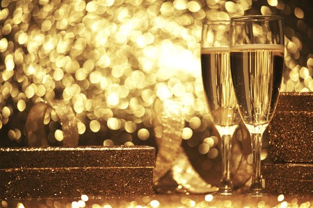 event party festive: Two champagne glasses with gift boxes over shiny bokeh background Stock Photo