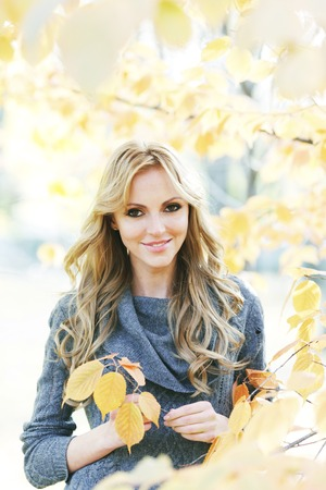 Portrait of beautiful young woman outdoors in autumn park photo