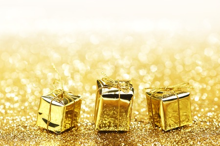 Gold decorative boxes with holiday gifts on abstract gold background with white copy space photo