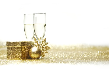 Champagne glasses and christmas decor on glitters with white copy space photo