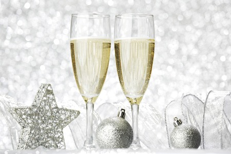 Two champagne glasses and christmas decoration on silver bokeh background photo