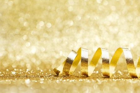 Golden curly ribbon decoration on glitter background close-up