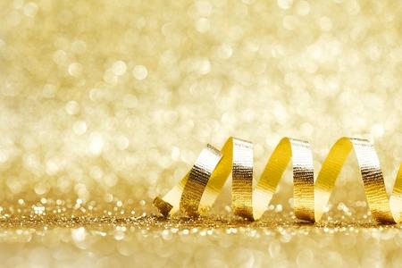 De gouden krullende lintdecoratie schittert achtergrondclose-up Stockfoto - 33034274